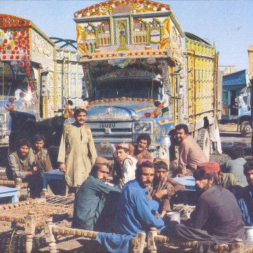 Men sitting in front of their decorated heavy trucks in Pakistan